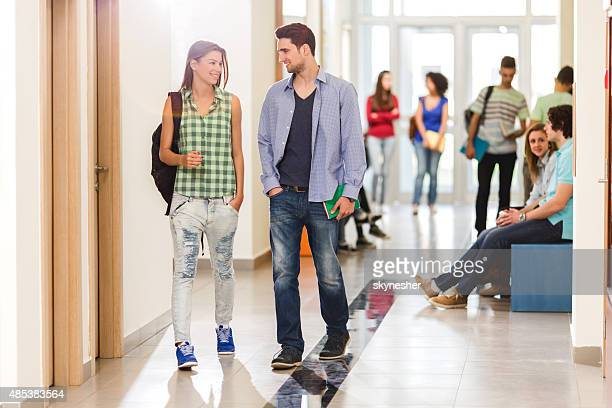 Young couple walking in school lobby and communicating.