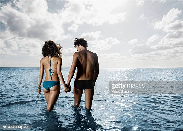 Young couple walking in sea, rear view