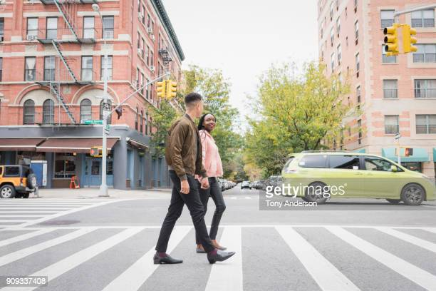 young couple walking in the city - pedestrian crossing stock photos and pictures
