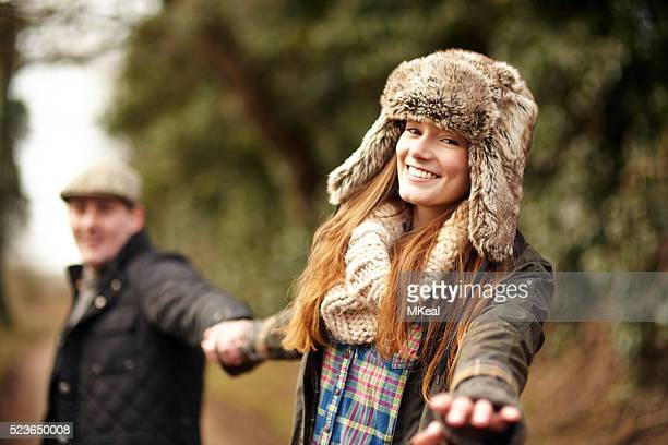 Young couple walking in the country hand-in-hand while the girl reaches out to the camera.