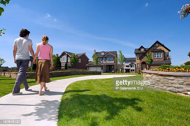 young couple walking in the suburbs towards a house - community building stock pictures, royalty-free photos & images