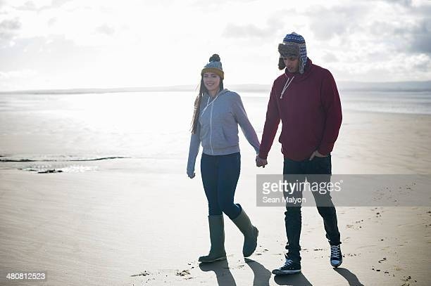 Young couple walking on beach, Brean Sands, Somerset, England