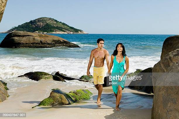 Young couple walking on beach, holding hands
