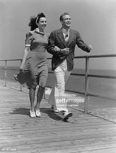 Young Couple Walking On Boardwalk