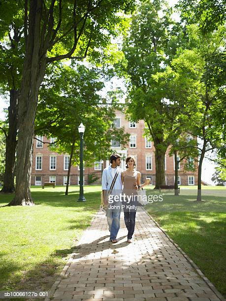 Young couple walking on pavement, university building in background