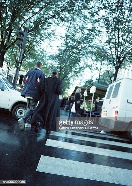 young couple walking on pedestrian crossing, rear view - passeren stockfoto's en -beelden