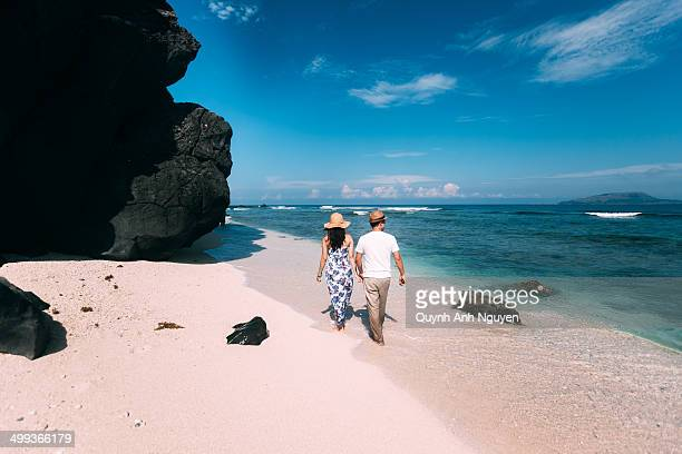 young couple walking on the beach - quảng ngãi stockfoto's en -beelden