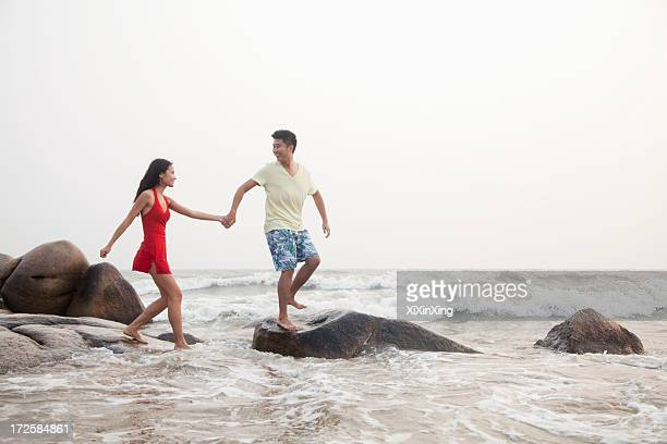 Young couple walking on the beach walking over rocks