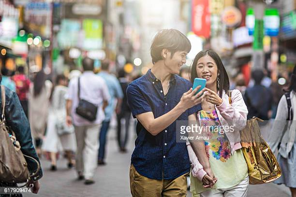 Young couple walking on the street with mobile phone