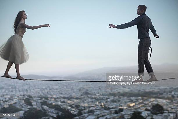 Young couple walking on tightrope
