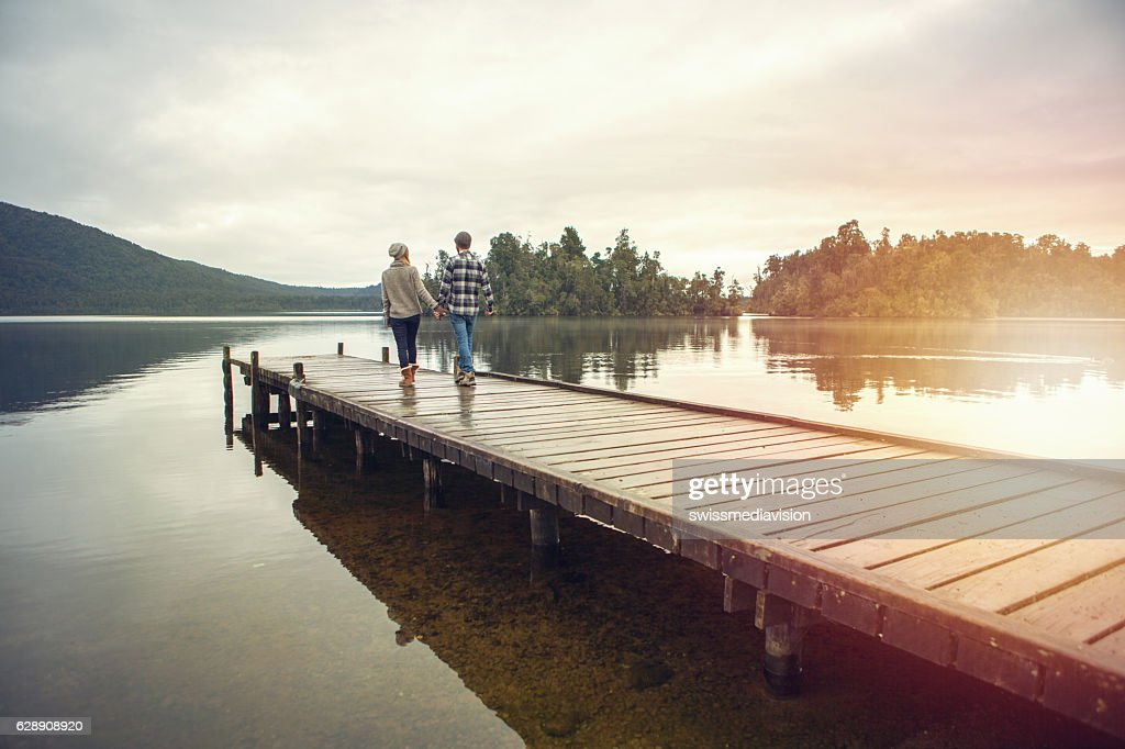 Young couple walking on wooden pier above lake : Stock Photo