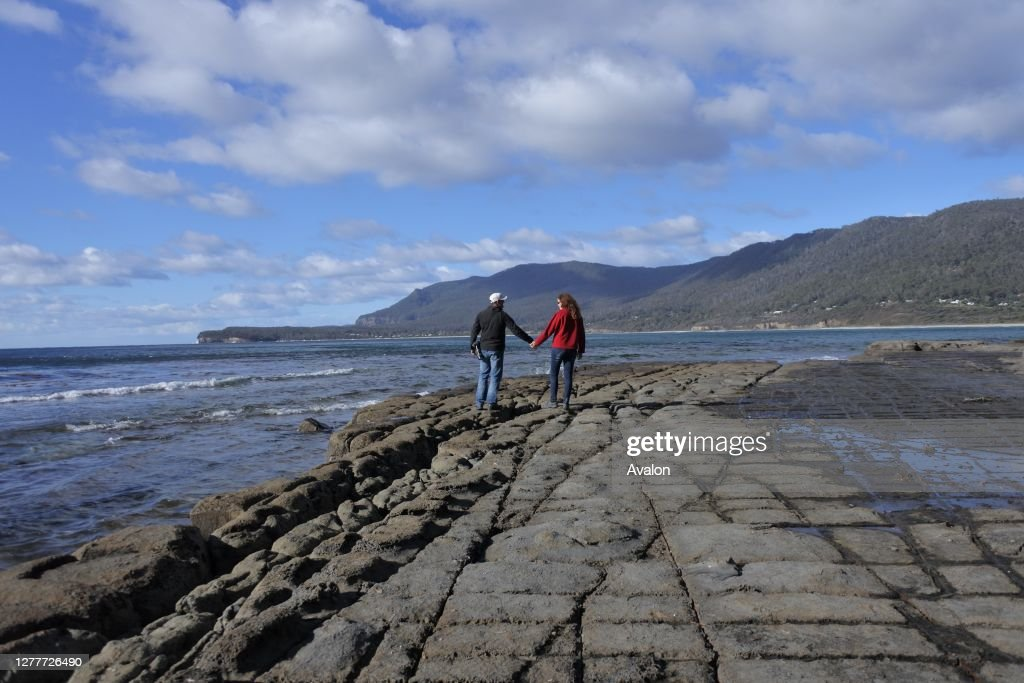 Young couple walking over the Tessellated Pavement in Tasman Peninsula Tasmania Australia. : News Photo