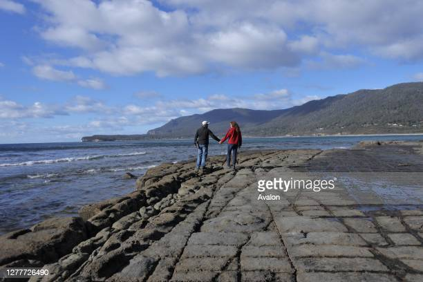 Young couple walking over the Tessellated Pavement in Tasman Peninsula Tasmania Australia.