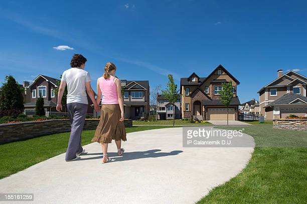 Young couple walking to their new suburban house.