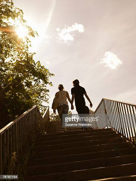 A young couple walking up the stairs outside Sweden.