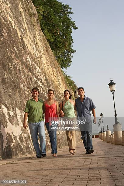 young couple walking with a mid adult man and a mature man - san juan stock pictures, royalty-free photos & images