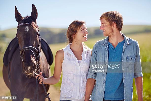 Young couple walking with horse on the countryside