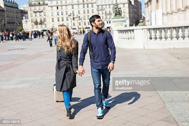 Jeune Couple marchant avec les bagages dans une ville européenne