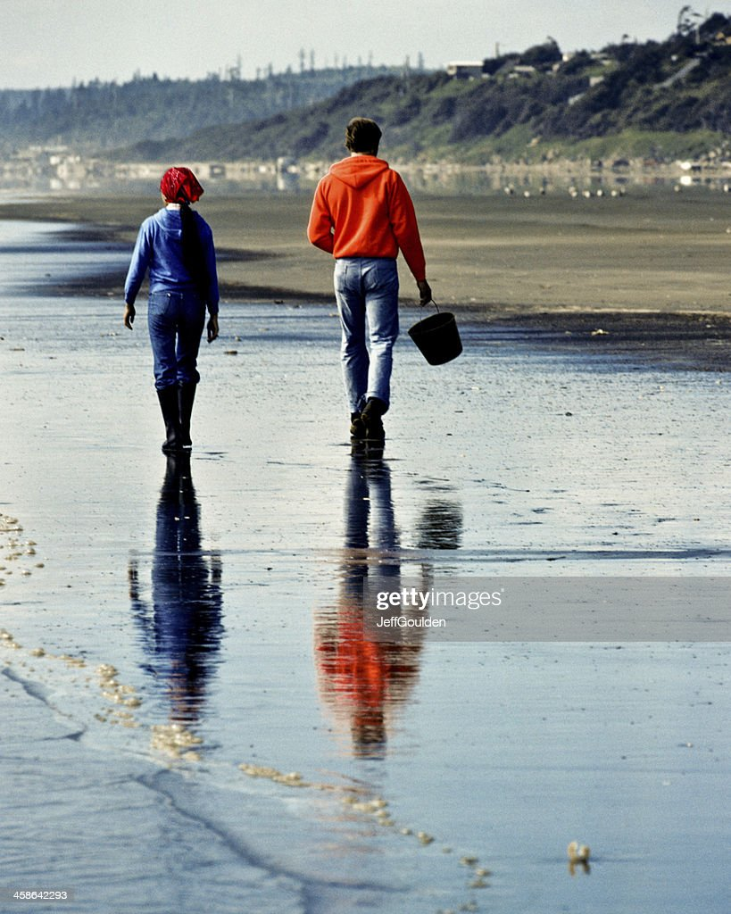 Young Couple Walking on Beach is Reflected in Wet  Sand : Stock Photo