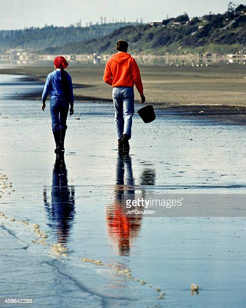 Young Couple Walking on Beach is Reflected in Wet  Sand