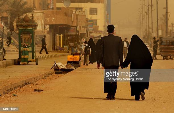Young couple walks hand in hand down a street near the Imam Ali Shrine on February 26, 2012 in Najaf, Iraq. After Mecca and Medina, Najaf is the...