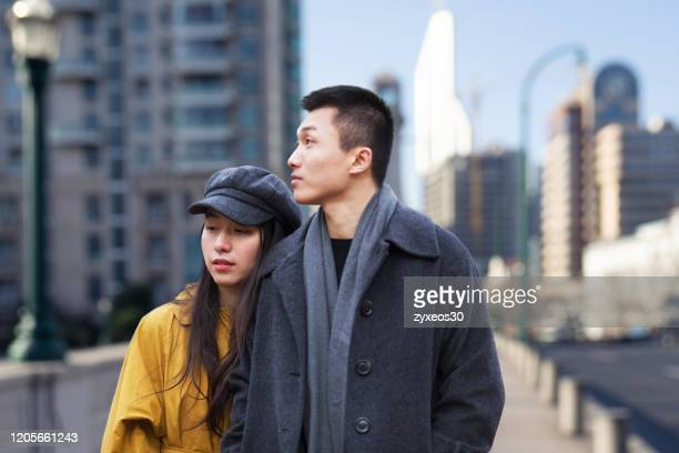 a young couple walks through the streets of shanghai,china - east asia, - china east asia stock pictures, royalty-free photos & images