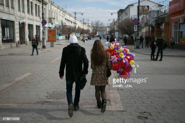 A young couple walks with colourful balloons in the centre of Simferopol on March 14 two days ahead of the referendum over Crimea's bid to break away...