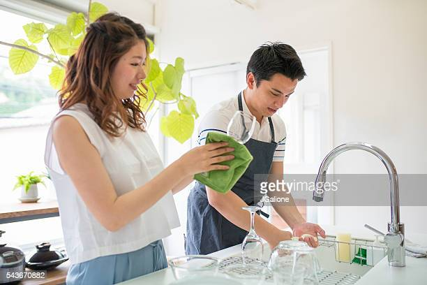 young couple washing dishes together in the kitchen - couples showering stock pictures, royalty-free photos & images
