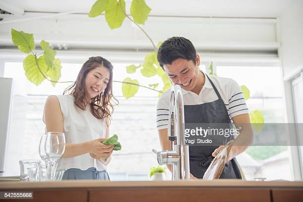 Young couple washing dishes together.