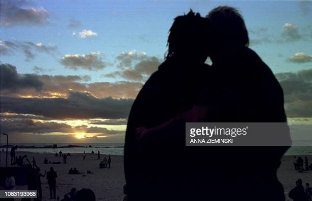 A young couple watch the last sunset of the 1990s on Camps Bay beach Cape Town 31 December 1999 The city was set to party the new year in