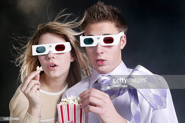 young couple watching 3d movie with popcorn