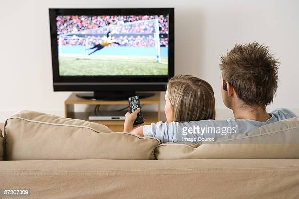 A young couple watching a football match on the tv