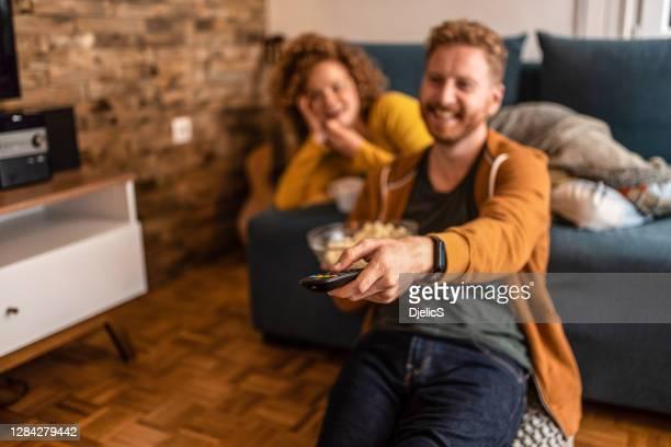 jong paar dat een film thuis bekijkt. - alleen volwassenen stockfoto's en -beelden