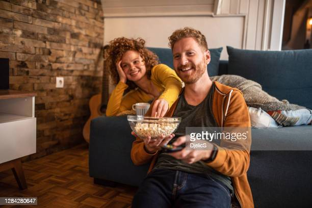 young couple watching a movie at home. - film stock pictures, royalty-free photos & images