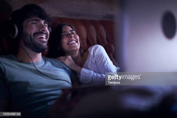young couple watching a movie on a laptop. - stream stock pictures, royalty-free photos & images