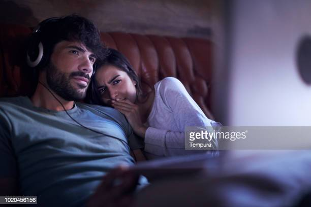 young couple watching a movie on a laptop. - scary movie stock photos and pictures