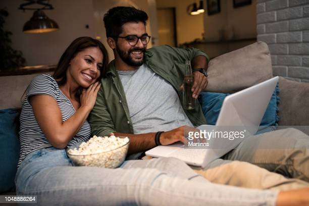 young couple watching a movie on a laptop. - girlfriends films stock pictures, royalty-free photos & images