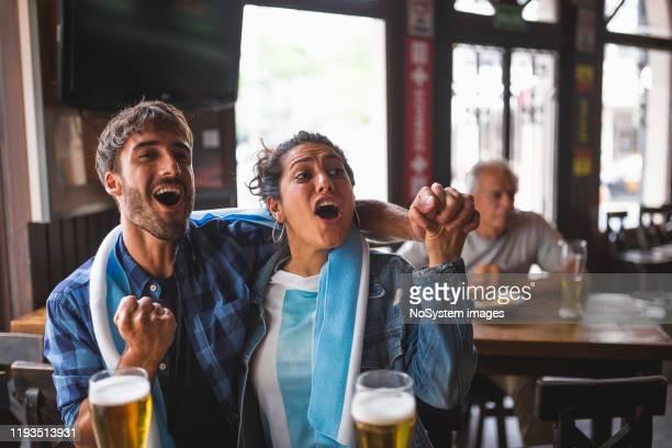 giovane coppia che guarda una partita di calcio in un pub locale - turno sportivo foto e immagini stock