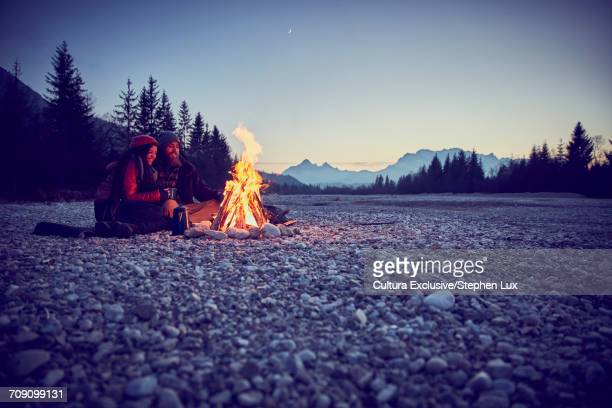 Young couple watching campfire by River Isar, Karwendel Mountains, Bavaria, Germany