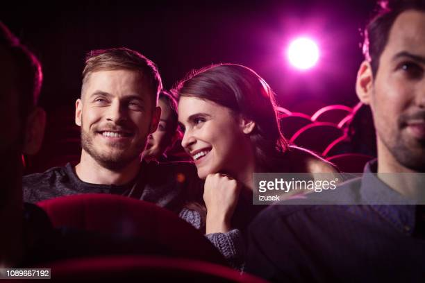 young couple watching comedy movie in the cinema - film industry stock pictures, royalty-free photos & images