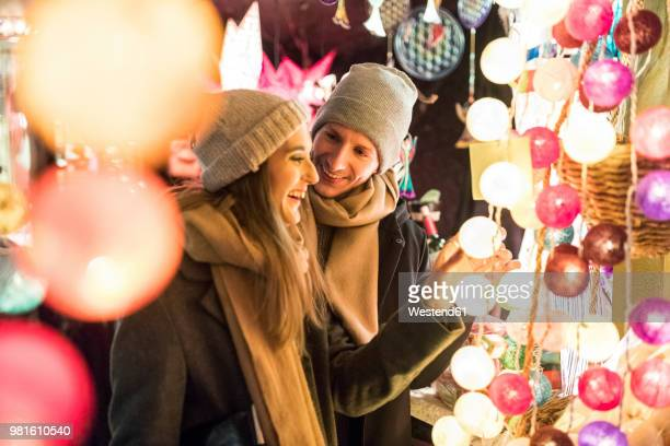 young couple watching offerings at christmas market - christmas market stock pictures, royalty-free photos & images