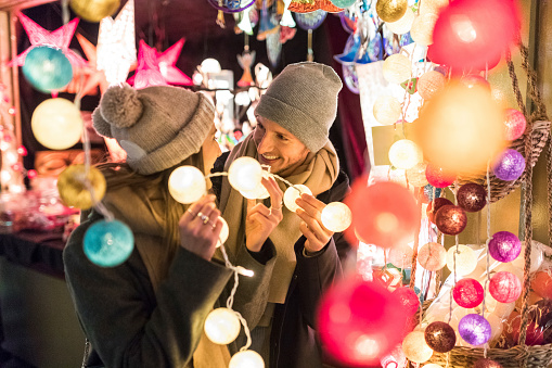 Young couple watching offerings at Christmas market - gettyimageskorea