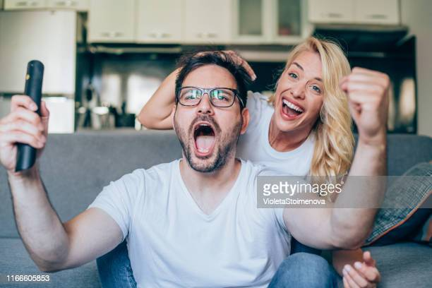 young couple watching sport on tv. - match sportivo foto e immagini stock
