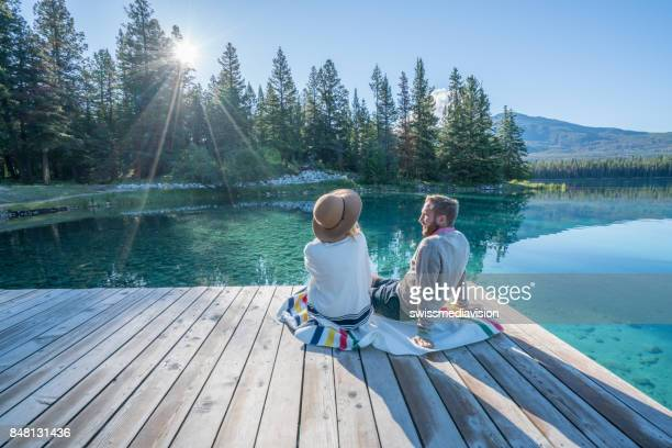young couple watching sunrise on lake pier - pier stock pictures, royalty-free photos & images