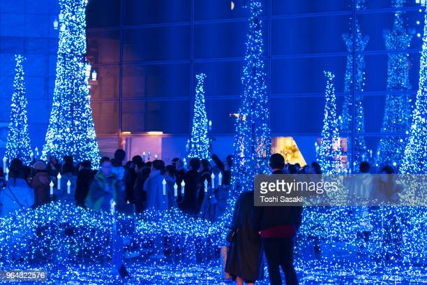 a young couple watching the caretta illumination show, which is illuminated by approximately 250,000 led lights every 20 minutes in caretta shopping mall shiodome tokyo japan on december 26 2017. - フェス ストックフォトと画像