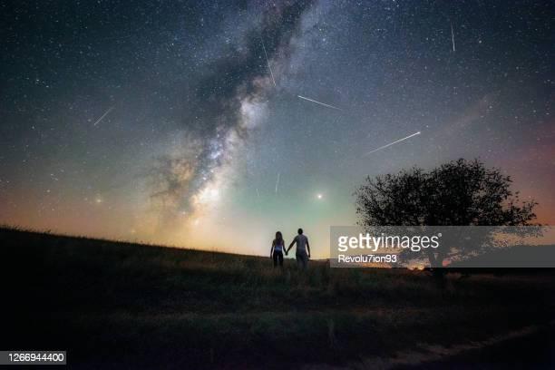 jong paar dat de meteorenregen perseïden en de melkweg let - astronomie stockfoto's en -beelden