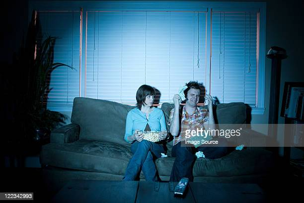 Young couple watching tv, man crying