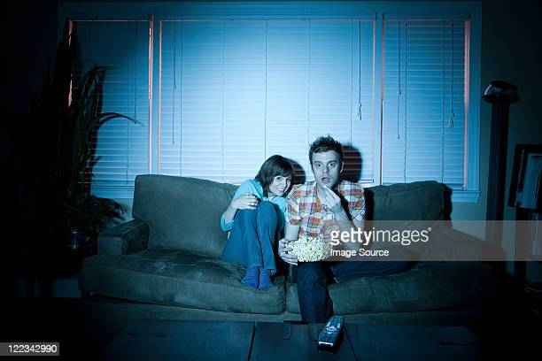young couple watching tv, man eating popcorn - scary movie stock photos and pictures