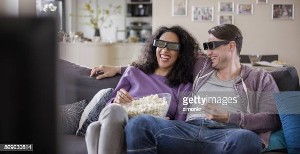 Young couple watching TV with 3D glasses