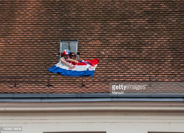 Young couple watching welcome celebration Croatian soccer from the roof window